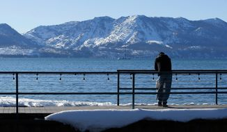 File - In this March 5, 2018 file photo, snow covers the mountain tops over looking Lake Tahoe in South Lake Tahoe, Calif. Californians close out their rainy season with the break they were hoping for, as a series of late-winter storms ease drought conditions that had been setting in again. (AP Photo/Rich Pedroncelli, File)