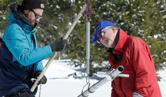 File - In this March 5, 2018, file photo, Frank Gehrke, chief of the California Cooperative Snow Surveys Program for the Department of Water Resources, right, reads the weight of the snow sample, on a scale held by Dylan Chapple, a fellow with the California Council of Science and Technology, during a supplemental snow survey near Echo Summit, Calif. Californians close out their rainy season with the break they were hoping for, as a series of late-winter storms ease drought conditions that had been setting in again. (AP Photo/Rich Pedroncelli, File)