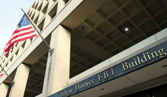 In this Nov. 2, 2016, file photo, the FBI's J. Edgar Hoover headquarter building in Washington. (AP Photo/Cliff Owen, File)  **FILE**