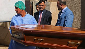 Pradeep Singh Rajpurohit, center, India's Ambassador to Iraq, watches while a casket holding one of 38 Indians abducted by the Islamic State group in 2014, that were found in a mass grave outside Mosul, is loaded on a truck to be transported from Baghdad's main morgue to the Baghdad airport, in Iraq, Sunday, April 1, 2018. The remains of the Indian construction workers captured and killed by IS militants in northern Iraq have been handed over to Indian authorities in Baghdad and will be flown home. (AP Photo/Khalid Mohammed)