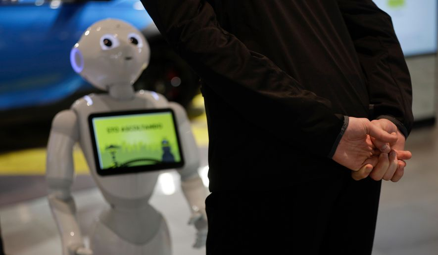 In this photo dated March 12, 2018, a guests asks robot Robby Pepper for information at the front desk of hotel in Peschiera del Garda, northern Italy. Robby Pepper, billed as Italy's first robot concierge, has been programed to answer simple guest questions in Italian, English and German, the humanoid, speaking robot will be deployed all season at a hotel on the popular Garda Lake to help relieve the desk staff of simple, repetitive questions. (AP Photo/Luca Bruno) ** FILE **