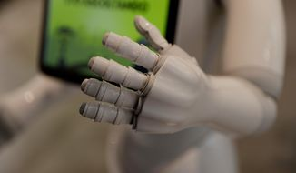In this photo dated March 12, 2018, robot Robby Pepper's hand is seen in the foreground as it welcomes guests at the front desk of hotel in Peschiera del Garda, northern Italy. Robby Pepper, billed as Italy's first robot concierge, has been programed to answer simple guest questions in Italian, English and German, the humanoid, speaking robot will be deployed all season at a hotel on the popular Garda Lake to help relieve the desk staff of simple, repetitive questions. (AP Photo/Luca Bruno)