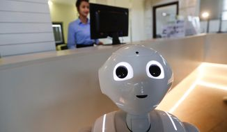 In this photo dated March 12, 2018, robot Robby Pepper stands at the front desk of hotel in Peschiera del Garda, northern Italy, Monday, March 12, 2018. Robby Pepper, billed as Italy's first robot concierge, has been programed to answer simple guest questions in Italian, English and German, the humanoid, speaking robot will be deployed all season at a hotel on the popular Garda Lake to help relieve the desk staff of simple, repetitive questions. (AP Photo/Luca Bruno)