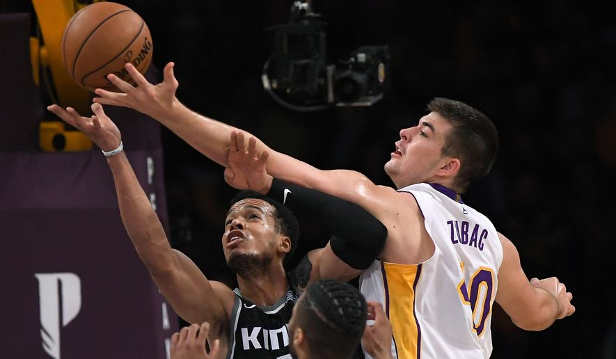 Sacramento Kings forward Skal Labissiere, left, and Los Angeles Lakers center Ivica Zubac reach for a rebound during the first half of an NBA basketball game Sunday, April 1, 2018, in Los Angeles. (AP Photo/Mark J. Terrill)