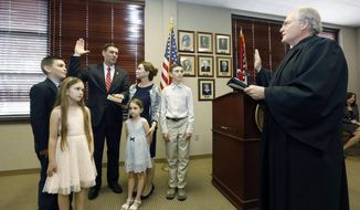 Mississippi Commissioner of Agriculture and Commerce Andy Gipson, is sworn into office by Mississippi Supreme Court Chief Justice William Waller Jr., right, as Gipson's family watch, during a ceremony involving friends, family, and neighbors, Monday, April 2, 2018, at the agency's building in Jackson, Miss. Gipson succeeds Cindy Hyde-Smith, who was appointed to the U.S. Senate. The new commissioner will serve the remainder of the four-year term. (AP Photo/Rogelio V. Solis)