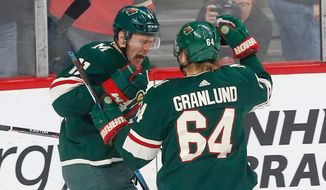Minnesota Wild's Zach Parise, left, celebrates his unassisted goal against the Edmonton Oilers goalie Cam Talbot with Mikael Granlund of Finland in the first period of an NHL hockey game Monday, April 2, 2018, in St. Paul, Minn. (AP Photo/Jim Mone)