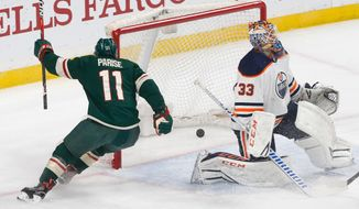 Minnesota Wild's Zach Parise, left, scores on Edmonton Oilers' goaltender Cam Talbot in the first period of an NHL hockey game Monday, April 2, 2018, in St. Paul, Minn. (AP Photo/Jim Mone)