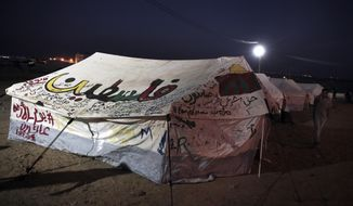 """A man walks next to a tent with a painting with Arabic writing that reads, """"Palestine,"""" near the Gaza Strip border with Israel, in eastern Gaza City, Sunday, April 1, 2018. Israel's defense minister on Sunday rejected international calls for an investigation into deadly violence along Gaza's border with Israel, saying troops acted appropriately and fired only at Palestinian protesters who posed a threat. (AP Photo/ Khalil Hamra)"""