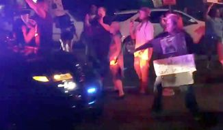 This March 31, 2018 photo made from video by Guy Danilowitz shows a woman holding her arm out as a Sacramento County Sheriff's patrol vehicle approaches during a demonstration over the shooting of an unarmed black man by Sacramento police. Sacramento County Sheriff Scott Jones said Monday, April 2, 2018 the driver likely didn't know he hit someone. Jones showed dashboard video from cruiser at the news conference, but didn't release it publicly. The sheriff's department said the protester suffered minor injuries. (Guy Danilowitz via AP)