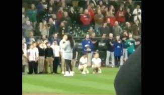 Two elementary school students took a knee during their choir's performance of the national anthem before Easter Sunday's game between the Seattle Mariners and the Cleveland Indian. (Twitter/@louispenna)