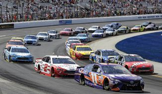 FILE - In this July 16, 2017, file photo, driver Denny Hamlin (11) leads the pack during the NASCAR Cup Series auto race at the New Hampshire Motor Speedway in Loudon, N.H. Owners of the speedway face an April 2018 court challenge over plans to bring in a country music festival to the venue after it lost a top-tier NASCAR race to Las Vegas. (AP Photo/Charles Krupa)