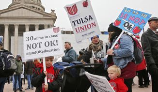 Keagan Nedrow, left, and Reed Nedrow, bottom right, stand with their mother, Tara Nedrow, right, who teaches history at Union High School, and other teachers, during a teacher rally against low school funding at the state Capitol Oklahoma City, Monday, April 2, 2018. (AP Photo/Sue Ogrocki)