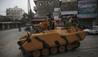 Turkish soldiers atop an armored personnel carrier patrol the northwestern city of Afrin, Syria, during a Turkish government-organized media tour into northern Syria, Saturday, March 24, 2018. (AP Photo/Lefteris Pitarakis) ** FILE **
