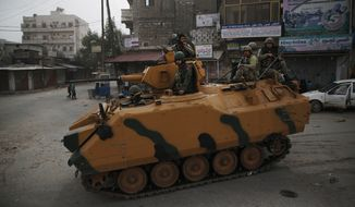 Turkish soldiers atop an armoured personnel carrier patrol the northwestern city of Afrin, Syria, during a Turkish government-organised media tour into northern Syria, Saturday, March 24, 2018.Turkey and allied Syrian opposition fighters captured the city of Afrin on Sunday, March 18, nearly two months after the launch of an operation to clear the area of the main Syrian Kurdish militia known as the People's Protection Units or YPG. Turkey considers the YPG a terror group and an extension of Kurdish rebels waging an insurgency within its own borders. (AP Photo/Lefteris Pitarakis)