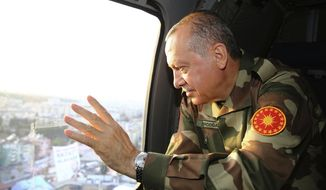 Turkey's President Recep Tayyip Erdogan, in full military combat uniform, waves from a helicopter as he visits Turkish troops at Ogulpinar border gate with Syria, near Reyhanli, Hatay, Turkey, Sunday, April 1 2018. (Kayhan Ozer/Pool Photo via AP)