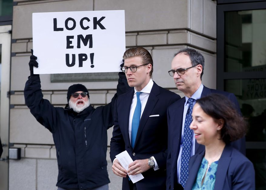 Alex van der Zwaan leaves Federal District Court in Washington, Tuesday, April 3, 2018. Holding the sign up is Bill Christeson from the Washington area. A federal judge sentenced Alex van der Zwaan to 30 days in prison. (AP Photo/Pablo Martinez Monsivais)