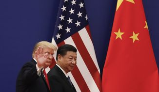 U.S. President Donald Trump waves next to Chinese President Xi Jinping after attending a business event at the Great Hall of the People in Beijing, Thursday, Nov. 9, 2017. Trump is on a five-country trip through Asia traveling to Japan, South Korea, China, Vietnam and the Philippines. (AP Photo/Andy Wong)