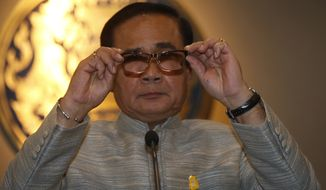 Thailand's Prime Minister Prayuth Chan-ocha holds his glasses before a press conference at Government house in Bangkok, Thailand, Tuesday, March 27, 2018. (AP Photo/Sakchai Lalit)