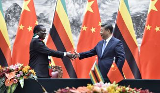 Zimbabwean President Emmerson Mnangagwa, left, shakes hands with Chinese President Xi Jinping as they pose for the media after a signing ceremony at the Great Hall of the People in Beijing, China, April 3, 2018. (Parker Song/Pool Photo via AP)