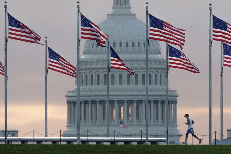 In this Sept. 27, 2017, photo, a early morning runner crosses in front of the U.S. Capitol as he passes the flags circling the Washington Monument in Washington. Congress is considering letting President Donald Trump roll back some of the $1.3 trillion federal spending package as Republicans in the House and Senate get hammered politically by conservatives for having approved the big spending bill. Rolling back the funds would be a highly unusual move and could put some lawmakers in the potentially uncomfortable position of having to vote for specific spending opposed by a president from their party. It would also offer Republicans a way to save face. (AP Photo/J. David Ake, File)