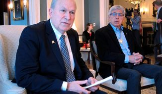 Alaska Gov. Bill Walker, left, speaks to reporters during a press availability at the governor's mansion as Lt. Gov. Byron Mallott listens on Tuesday, April 3, 2018, in Juneau, Alaska. Walker addressed a range of topics, including trying to reach agreement with lawmakers on an overall budget plan. (AP Photo/Becky Bohrer)