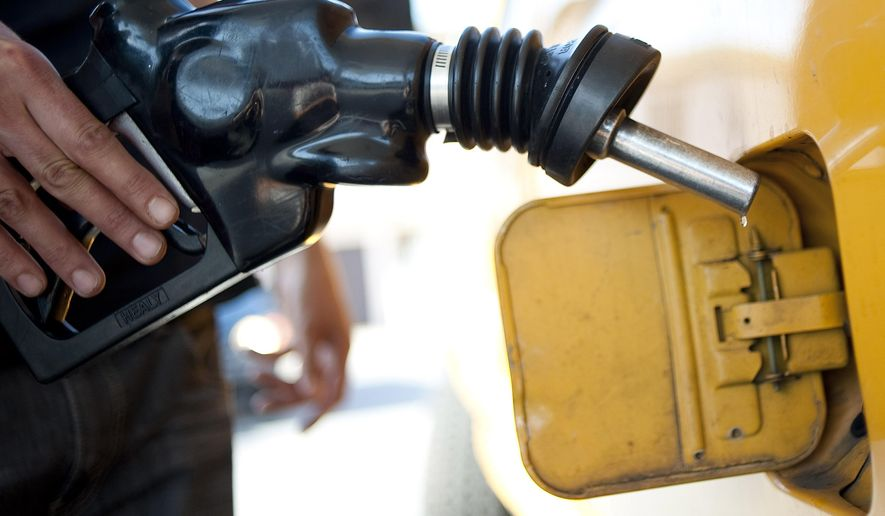 In this Aug. 10, 2012, file photo a customer pumps gas into his dual-tank pickup truck at a 76 gas station in Los Angeles. (AP Photo/Grant Hindsley, File)