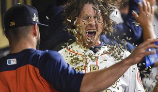 Houston Astros' Josh Reddick (22) is hit with sunflower seeds by Lance McCullers Jr. after Reddick hit a grand slam off Baltimore Orioles relief pitcher Nestor Cortes Jr. during the seventh inning of a baseball game, Tuesday, April 3, 2018, in Houston. (AP Photo/Eric Christian Smith)