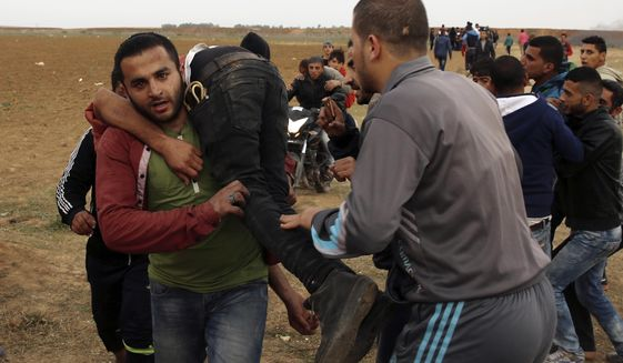 Palestinian protesters evacuate a wounded youth during clashes with Israeli troops along Gaza's border with Israel, east of Beit Lahiya, Gaza Strip, Tuesday, April 3, 2018. Israel's defense minister said Tuesday that the military will not change its tough response to Hamas-led mass protests, warning that those who approach the border are putting their lives at risk. Eighteen Palestinians were killed by Israeli fire last Friday, the first day of what Hamas says will be six weeks of intermittent border protests against a stifling blockade of the territory. (AP Photo/Adel Hana)