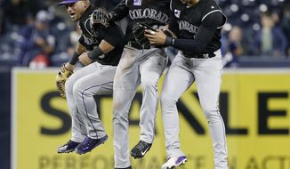 Colorado Rockies outfield, Gerardo Parra, left, Charlie Blackmon, center, and Carlos Gonzalez leap in celebration of the Rockies defeating the San Diego Padres 7-4 after the ninth inning of a baseball game in San Diego, Monday, April 2, 2018. (AP Photo/Alex Gallardo)