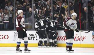 Los Angeles Kings players celebrate a goal by Torrey Mitchell as Colorado Avalanche's Nikita Zadorov, left, of Russia, and Colin Wilson skate near by during the first period of an NHL hockey game Monday, April 2, 2018, in Los Angeles. (AP Photo/Jae C. Hong)