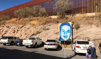 FILE--This file photo taken Monday, Dec. 4, 2017 shows the boundary in Nogales, Mexico, with the United States and a poster of Juan Antonio Elena Rodriguez, a teen who was shot and killed across the line by a Border Patrol agent in 2010. The jury in a federal trial of a U.S. Border Patrol agent charged with second-degree murder quietly visited the international line in Nogales after dark last week to see what the officer did the night Rodriguez was killed in a cross-border shooting. (AP Photo/Anita Snow, file)