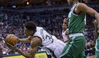 Milwaukee Bucks forward Giannis Antetokounmpo, left, falls to the floor as he is defended by Boston Celtics forward Al Horford, right, during the first half of an NBA basketball game Tuesday, April 3, 2018, in Milwaukee. (AP Photo/Darren Hauck)