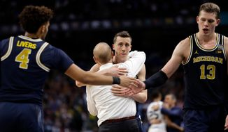 Michigan's Duncan Robinson hugs head coach John Beilein during the second half in the championship game of the Final Four NCAA college basketball tournament against Villanova, Monday, April 2, 2018, in San Antonio. (AP Photo/Eric Gay)