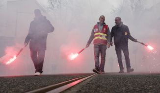 Railway employees hold flares during a demonstration in Lyon, central France, Tuesday, April 3, 2018. A major French railway strike brought the country's famed high-speed trains to a halt Tuesday, leaving passengers stranded or scrambling for other options _ and posing the biggest test so far for President Emmanuel Macron's economic strategy. (AP Photo/Laurent Cipriani)