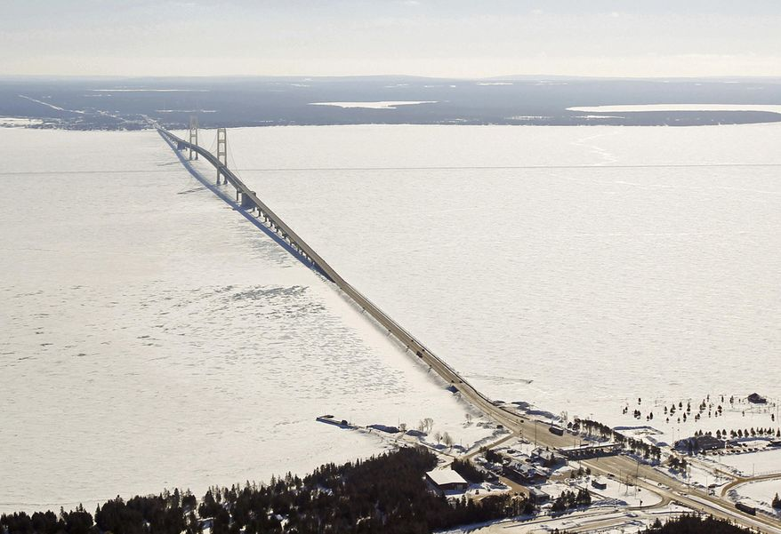 FILE - This Feb. 11, 2014 aerial file photo shows a view of the Mackinac Bridge, which spans a 5-mile-wide freshwater channel called the Straits of Mackinac that separates Michigan's upper and lower peninsulas. Officials say hundreds of gallons of potentially toxic coolant fluid have leaked from electric power cables in the waterway that links Lake Huron and Lake Michigan. (Keith King/Traverse City Record-Eagle via AP, Pool, File)