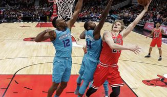 Chicago Bulls' Lauri Markkanen, right, scores over Charlotte Hornets' Dwight Howard (12) and Michael Kidd-Gilchrist (14) during the first half of an NBA basketball game Tuesday, April 3, 2018, in Chicago. (AP Photo/Charles Rex Arbogast)