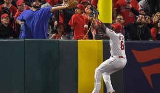 A fan reaches for a ball hit for an inside-the-park home run by Cleveland Indians' Edwin Encarnacion along with Los Angeles Angels left fielder Justin Upton during the second inning of a baseball game Monday, April 2, 2018, in Anaheim, Calif. (AP Photo/Mark J. Terrill)