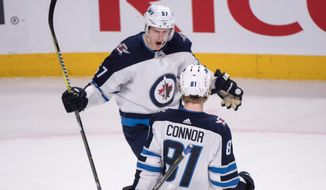 Winnipeg Jets' Tyler Myers congratulates teammate Kyle Connor after Connor scored the winning goal during overtime to defeat the Montreal Canadiens 5-4 in NHL hockey action Tuesday, April 3, 2018 in Montreal. (Paul Chiasson/The Canadian Press via AP)