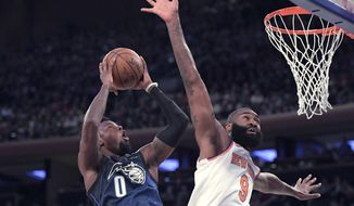 Orlando Magic guard Jamel Artis (0) attempts a shot as New York Knicks center Kyle O'Quinn (9) defends during the first quarter of an NBA basketball game Tuesday, April 3, 2018, at Madison Square Garden in New York. (AP Photo/Bill Kostroun)