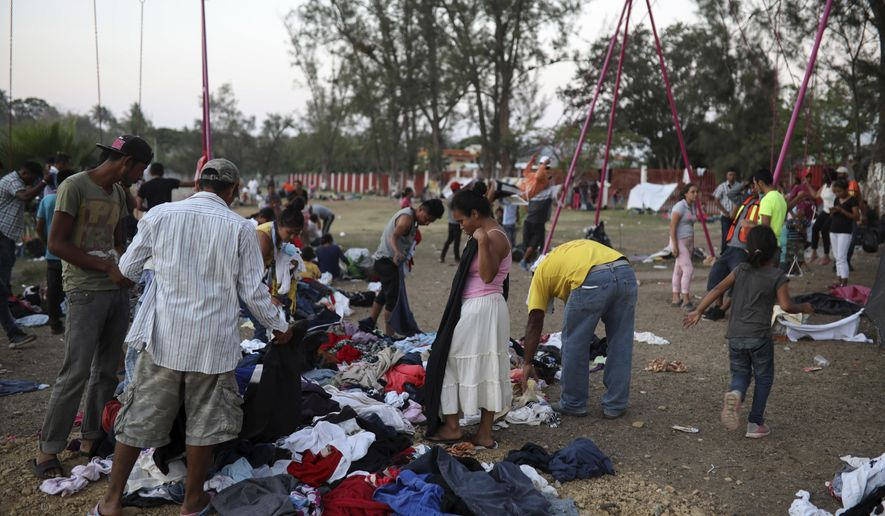 Central American migrants participating in the Migrant Stations of the Cross caravan search through donated clothing during the caravan's few-day's stop at a sports center in Matias Romero, Oaxaca state, Mexico, late Monday, April 2, 2018. The annual caravans have been held in southern Mexico for years as an Easter-season protest against the kidnappings, extortion, beatings and killings suffered by many Central American migrants as they cross Mexico. (AP Photo/Felix Marquez)