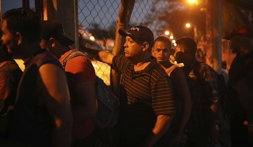 "Central American migrants stand in line for food during the annual Migrant Stations of the Cross caravan or ""Via crucis,"" organized by the ""Pueblo Sin Fronteras"" activist group, as the caravan makes a few-days stop at a sports center in Matias Romero, Oaxaca state, Mexico, late Monday, April 2, 2018. The annual caravans have been held in southern Mexico for years as an Easter-season protest against the kidnappings, extortion, beatings and killings suffered by many Central American migrants as they cross Mexico. (AP Photo/Felix Marquez)"