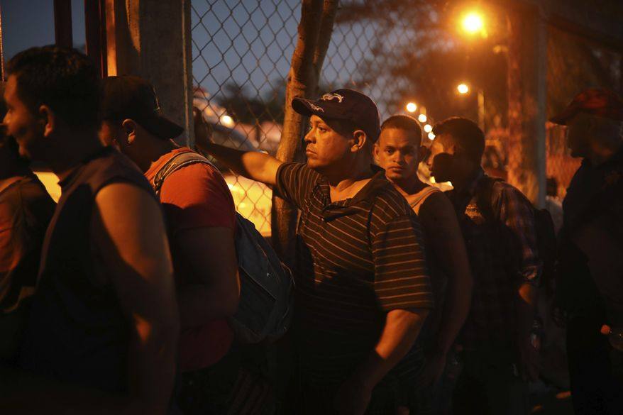 """Central American migrants stand in line for food during the annual Migrant Stations of the Cross caravan or """"Via crucis,"""" organized by the """"Pueblo Sin Fronteras"""" activist group, as the caravan makes a few-days stop at a sports center in Matias Romero, Oaxaca state, Mexico, late Monday, April 2, 2018. The annual caravans have been held in southern Mexico for years as an Easter-season protest against the kidnappings, extortion, beatings and killings suffered by many Central American migrants as they cross Mexico. (AP Photo/Felix Marquez)"""