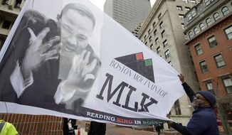 Steve Coachman, of Boston, unfurls a flag featuring a likeness of Martin Luther King Jr., Monday, April 2, 2018, before a remembrance on City Hall Plaza in Boston, for King who was assassinated 50 years ago this week. Dozens of speakers aged 5 to 91 took turns reading short passages from King's last speech during the remembrance. King originally delivered the speech in Memphis, Tennessee, on the eve of his April 4, 1968, death. (AP Photo/Steven Senne)