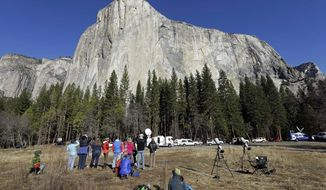 FILE - In this Jan. 14, 2015, file photo, spectators gaze at El Capitan for a glimpse of climbers Tommy Caldwell and Kevin Jorgeson, as seen from the valley floor in Yosemite National Park, Calif. The Interior Department is backing down from a plan to impose steep fee increases at popular national parks after widespread opposition from elected officials and the public. (AP Photo/Ben Margot, File)