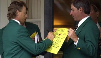 FILE - In this Tuesday, April 9, 2002, file photo, former two-time Masters Champion Bernhard Langer, left, signs an autograph for fellow former champion Fred Couples, right, at the Augusta National Golf Club prior to the annual Champions dinner at the 2002 Masters in Augusta, Ga. Even past champions aren't always sure where to sit at the dinner.  (AP Photo/Dave Martin, File)
