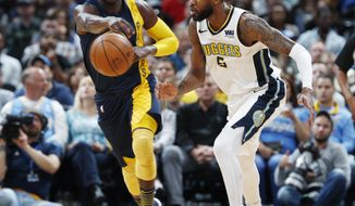 Indiana Pacers guard Victor Oladipo, left, passes the ball as Denver Nuggets forward Will Barton defends in the first half of an NBA basketball game Tuesday, April 3, 2018, in Denver. (AP Photo/David Zalubowski)
