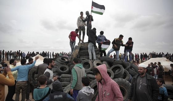 A protester holds a Palestinian flag on top of tires to be burned during an ongoing protest next to Gaza's border with Israel, east of Khan Younis, Gaza Strip, Tuesday, April 3, 2018. Israel's defense minister said Tuesday that the military will not change its tough response to Hamas-led mass protests, warning that those who approach the border are putting their lives at risk. Eighteen Palestinians were killed by Israeli fire last Friday, the first day of what Hamas says will be six weeks of intermittent border protests against a stifling blockade of the territory. (AP Photo/Khalil Hamra)
