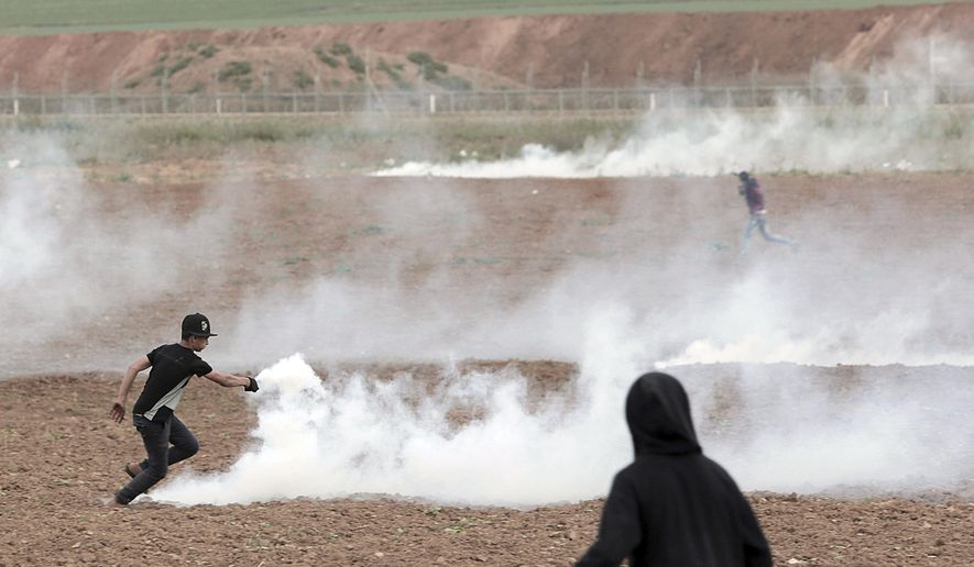 A Palestinian protester throws back teargas during clashes with Israeli troops along the Gaza's border with Israel, east of Beit Lahiya, Gaza Strip, Tuesday, April 3, 2018. Israel's defense minister said Tuesday that the military will not change its tough response to Hamas-led mass protests, warning that those who approach the border are putting their lives at risk. Eighteen Palestinians were killed by Israeli fire last Friday, the first day of what Hamas says will be six weeks of intermittent border protests against a stifling blockade of the territory. (AP Photo/Adel Hana)