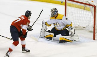 Florida Panthers center Derek MacKenzie (17) misses as Nashville Predators goaltender Pekka Rinne (35) defends in the second period in an NHL hockey game, Tuesday, April 3, 2018, in Sunrise, Fla. (AP Photo/Joe Skipper)