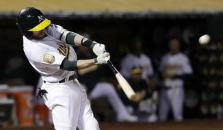 Oakland Athletics' Jed Lowrie drives in two runs with a double against the Texas Rangers during the seventh inning of a baseball game, Monday, April 2, 2018, in Oakland, Calif. (AP Photo/Marcio Jose Sanchez)